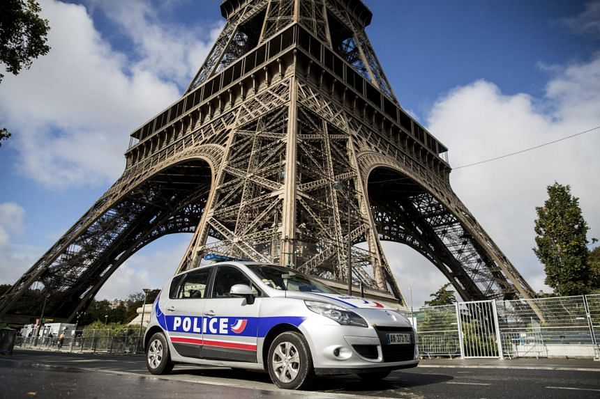 A French police car is parked in front of the Eiffel Tower in Paris.