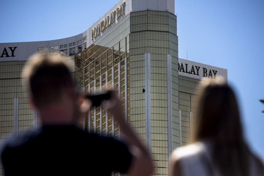 Pedestrians take photos of the broken windows on the 32nd floor where a gunman fired on an outdoor concert festival at the Mandalay Bay Resort and Casino in Las Vegas.