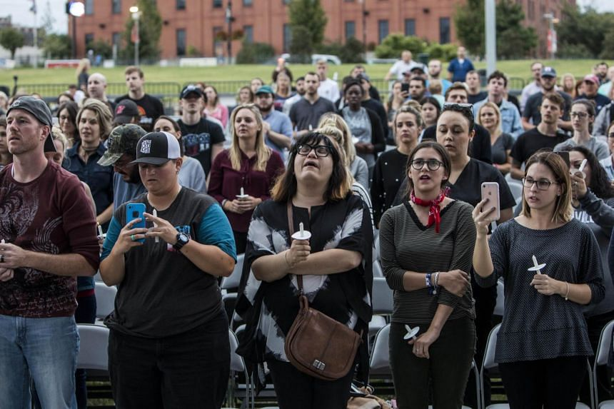People gather at the Ascend Amphitheater for a vigil honoring the victims of the mass shooting in Las Vegas, on Oct 2, 2017 in Nashville, Tennessee.