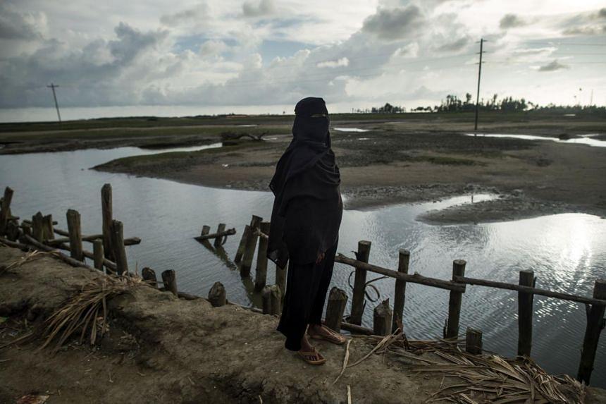 A Rohingya Muslim refugee stands on the river bank in Teknaf, Bangladesh.