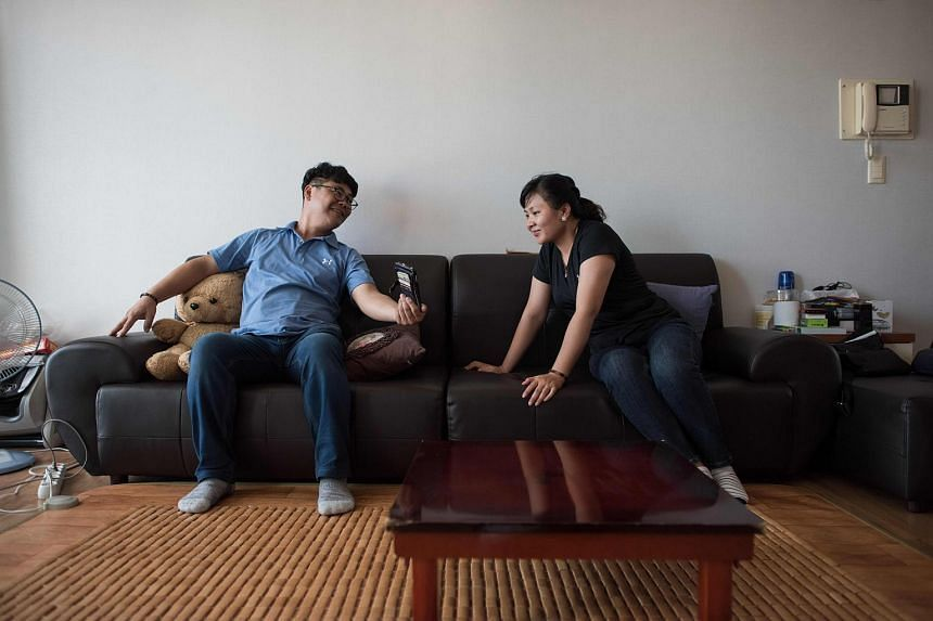 23-year-old Huynh Thi Thai Muoi (right) of Vietnam and her 43-year-old husband Kim Kyeong-Bok of South Korea looking at a mobile phone in their apartment in Gwangju on Aug 23, 2017.