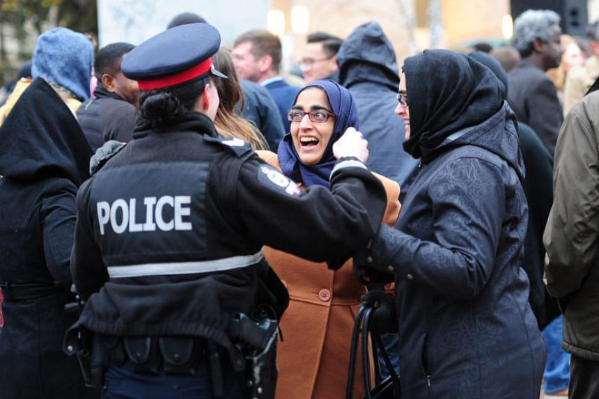 Muslim women speak to a police woman during a rally organised by the Alberta Muslim Public Affairs Council following an attack in Edmonton, Canada on Oct 1, 2017.