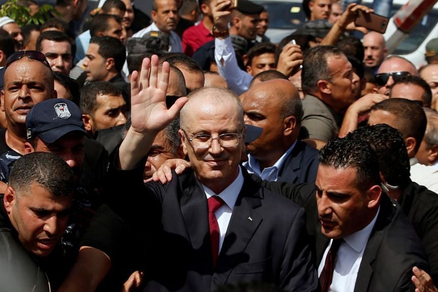 Palestinian Prime Minister Rami Hamdallah arrives with his government ministers to take control of Gaza from the Islamist Hamas group, in the northern Gaza Strip on Oct 2, 2017.