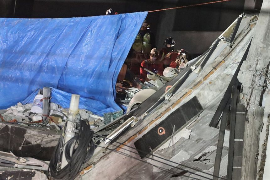 Members of rescue team place a blue tarp and a Mexican flag as they remove the last body trapped under rubble of a collapsed building.