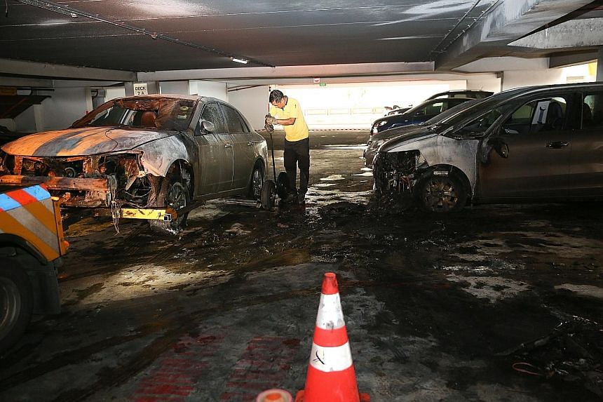 A car being towed away at the multistorey carpark at Block 141A in Toa Payoh Lorong 2, after three vehicles were involved in a fire at around 6.45am yesterday. The Singapore Civil Defence Force (SCDF), which put out the fire, said no one was injured