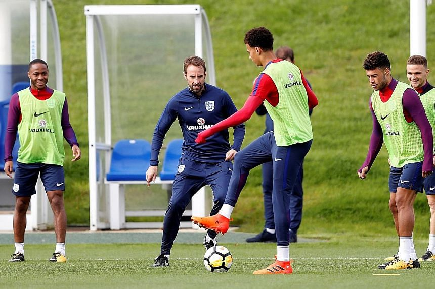 England manager Gareth Southgate enjoying a kick-about in training with members of his squad ahead of tomorrow's World Cup qualifier against Slovenia at Wembley. Midfielder Dele Alli (front) will play no part, having copped a one-match ban for his vu