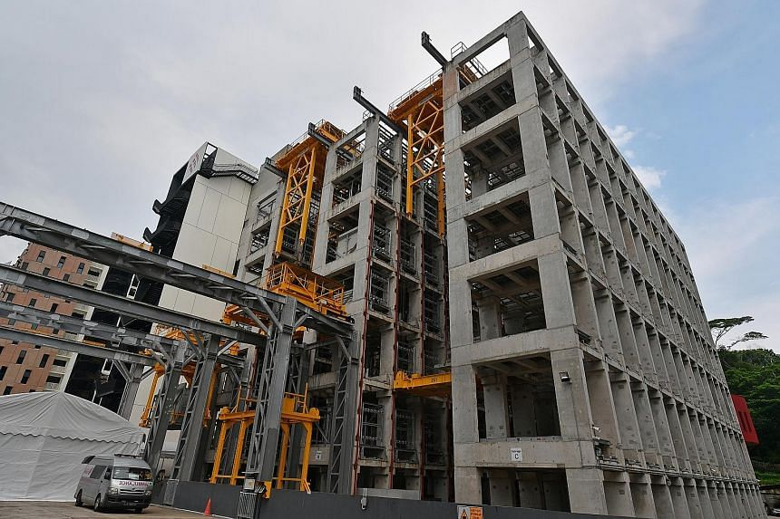 An automated precast storage facility at the integrated construction and prefabrication hub, Greyform Building, in Kaki Bukit. Such hubs optimise land use and require less time and fewer workers to build. Minister for Finance Heng Swee Keat viewing t