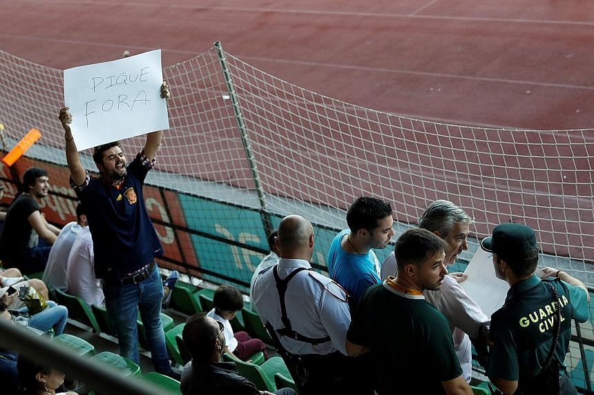 """A Civil Guard officer removes a banner critical of Spain's Gerard Pique, while another spectator holds a sign that says: """"Pique out"""" before a training session for the national team on Monday."""