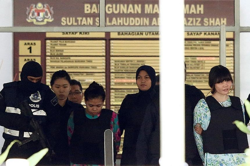 Police officers escorting Siti Aisyah (at left) and Doan Thi Huong as they left the Shah Alam High Court yesterday. The two women, who are on trial for Mr Kim Jong Nam's murder, allegedly smeared his face with the VX nerve agent at Terminal 2 of KLIA