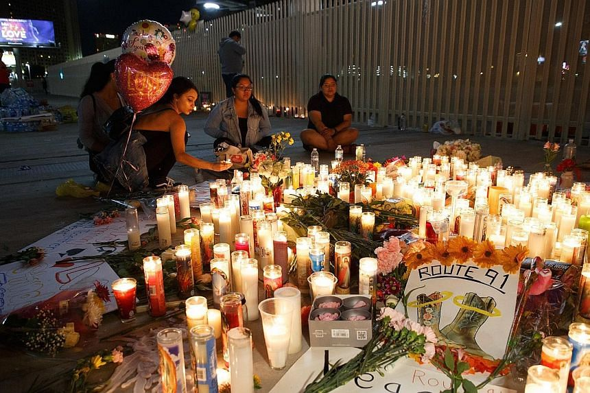 Mourners paying tribute to victims of the mass shooting at a makeshift memorial on the Las Vegas Strip on Monday. At least 59 people were killed and over 520 injured in the shooting that targeted crowds at the Route 91 Harvest country music festival