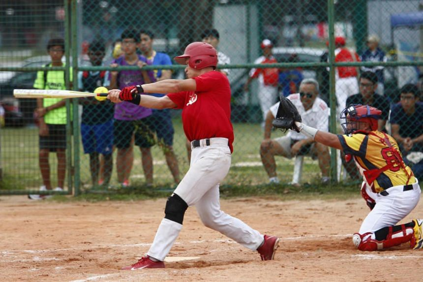 Singapore's Benjamin Oh (left) swings and misses the ball during the softball match at the Asian qualifier held at the Kallang Diamond on Dec 16, 2014.