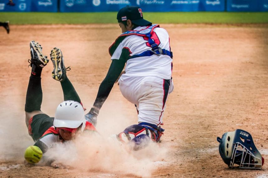 Yuka Ramadina's (left) sliding effort to reach home base was not enough to prevent Indonesia from losing 11-7 to Thailand in the 28th SEA Games, Women's Softball semi-finals at Kallang Softball Field on June 9,  2015.