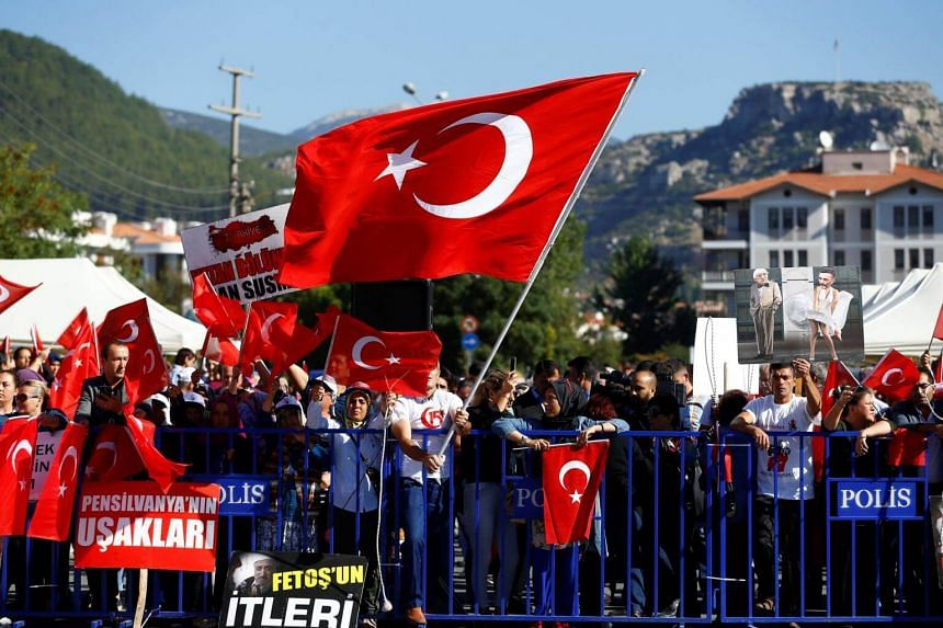 Supporters of President Tayyip Erdogan wave Turkish flags during a trial for soldiers accused of attempting to assassinate the president, in Mugla, Turkey on Oct 4, 2017.