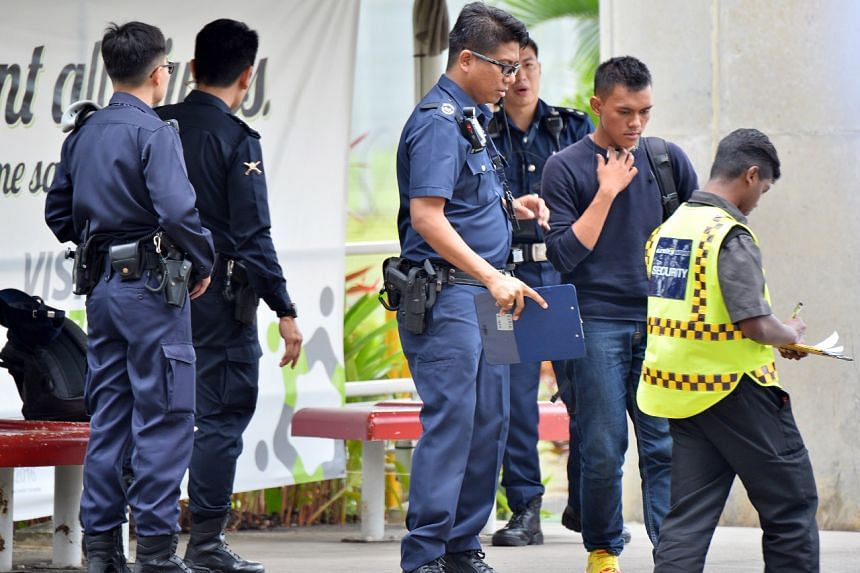 One (in blue shirt) of the two men apprehended when they were caught trying to enter SMRT Bishan depot without passes.