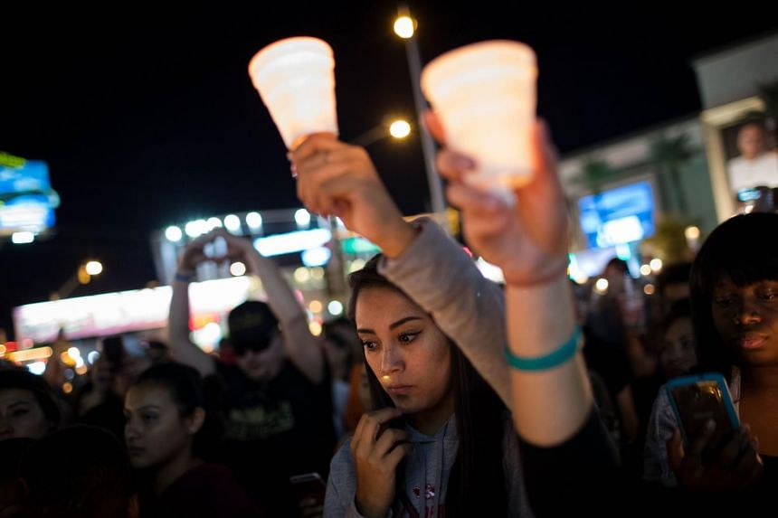 Mourners attend a candlelight vigil at the corner of Sahara Avenue and Las Vegas Boulevard for the victims of Sunday night's mass shooting, in Las Vegas, Nevada, on Oct 2, 2017.