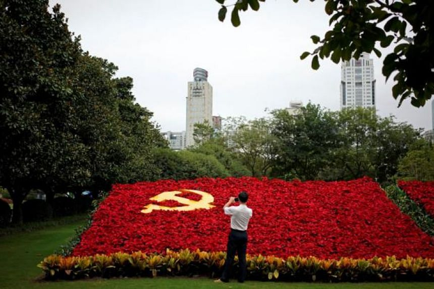 A man takes photos of a party flag of Communist Party of China made with flowers.
