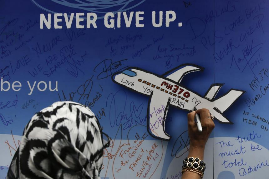 A woman writes messages for the passengers of missing Malaysia Airlines flight MH370 on a banner during a remembrance ceremony to mark the second anniversary of the plane's disappearance.
