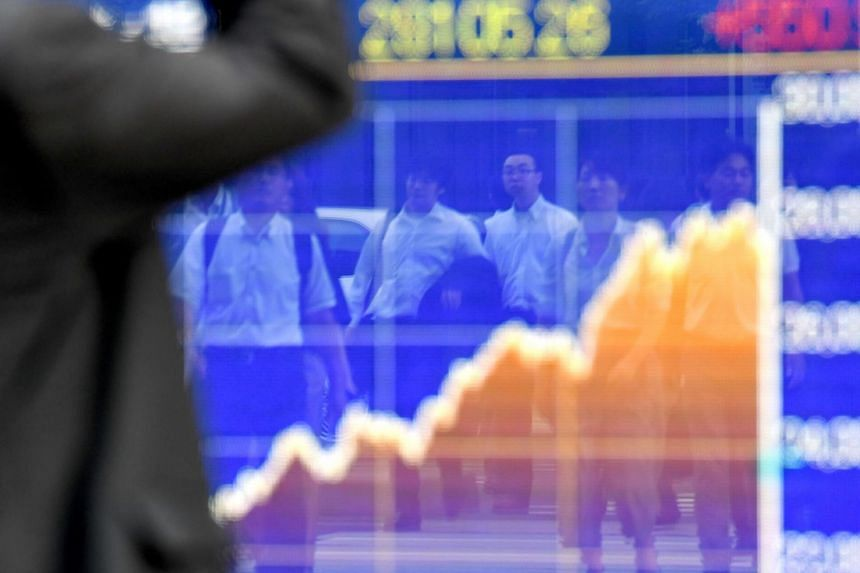 Pedestrians are reflected in the window of a securities company showing an electronics stock indicator in Tokyo.