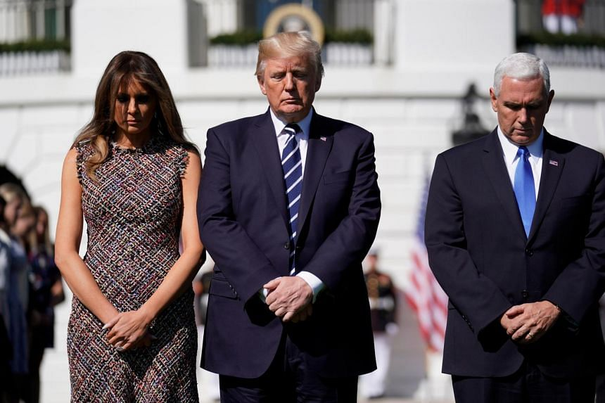US President Donald Trump stands with first lady Melania Trump and Vice President Mike Pence during a moment of silence in the wake of the the mass shooting in Las Vegas at the White House in Washington, on Oct 2, 2017.