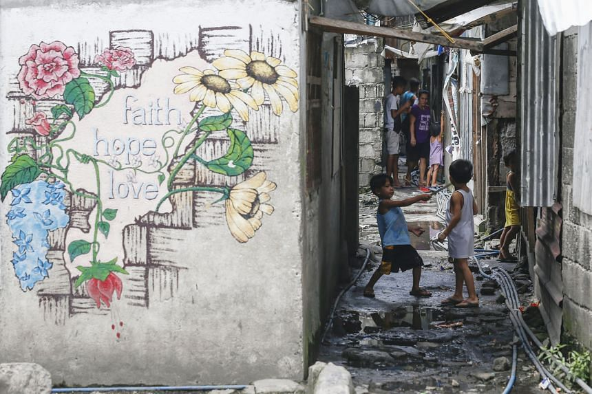 Filipino children in a slum district in Quezon City, east of Manila, yesterday. Data shows there are 250 million people in East Asia and the Pacific with poor-quality homes, limited access to basic services and at risk to hazards like flooding. China
