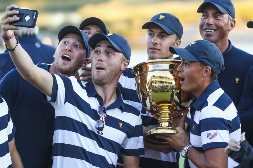 Justin Thomas takes a selfie with team mates as they pose with the Presidents Cup trophy, Oct 1, 2017.