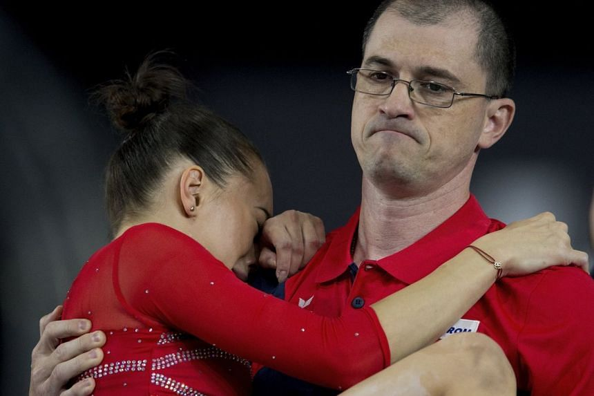 Iordache cries as her coach carries her from the floor exercise.