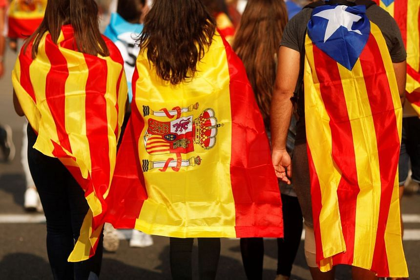 Youths in Barcelona wrapped in Catalan, Spanish and Estelada (Catalan separatist) flags.