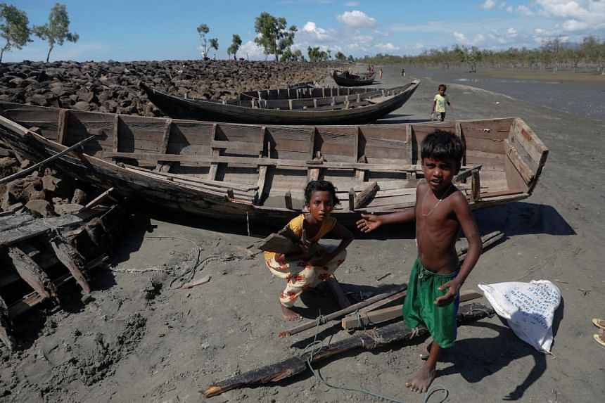 Children collect wood from remnants of some 20 boats that ferried Rohingya refugees fleeing violence in Myanmar.