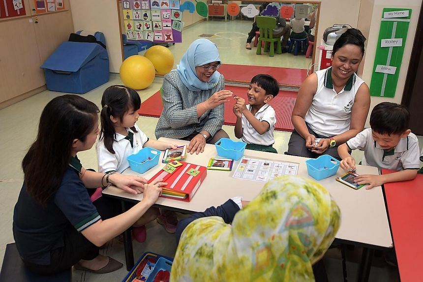 President Halimah Yacob interacting with six-year-olds (from left) Eureka Chong, Jothy Kanna Deepak and Ivan Ong at Rainbow Centre Yishun Park School. With them are (from far left) early intervention programme assistant director Janice Leong and teac