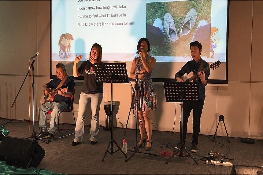 Ms Goh (second from far left) song-signing at the Story Carnival last month. With her are (from far left) Mr Jaffar Sidek, Ms Vivienne Wong and Mr Feng Lee. Telling stories using songs is a way of promoting deaf awareness, said Ms Goh. Ms Lily Goh at