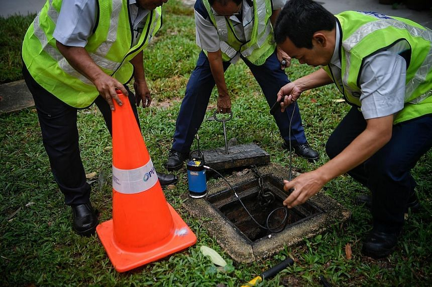 Above: PUB staff using a leak noise correlator to pinpoint the leak spot along the pipe at Block 222, Bukit Batok East Avenue 3, where a pipe burst on Sunday. Below: On Sept 26, a pipe leak sent up a fountain of water at the junction of Bukit Batok W