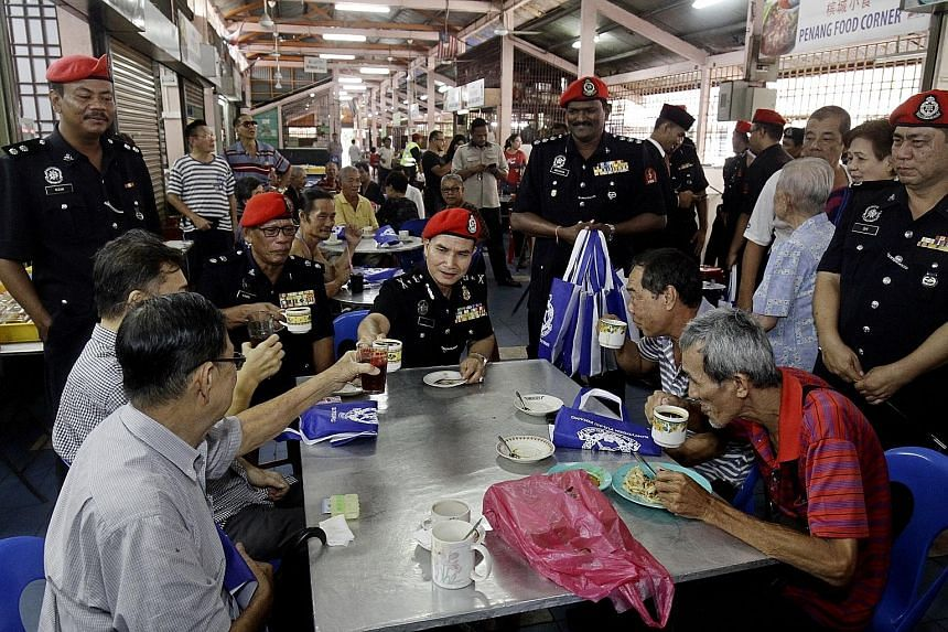 Federal Reserve Unit commander Wan Abdullah Ishak (centre) and other officials from Malaysia's riot police unit mingling with George Town residents on Tuesday as part of a community policing programme to forge closer ties with citizens and change pub