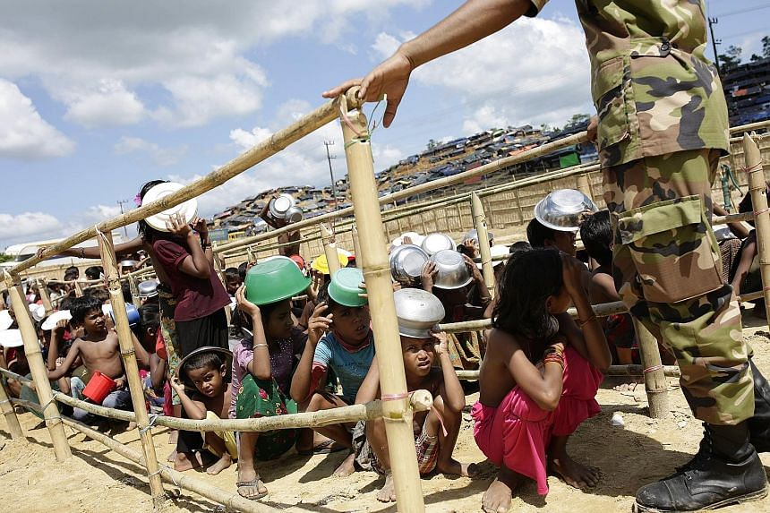 Rohingya children queueing to collect food in a camp in Ukhiya, Cox's Bazar, Bangladesh, yesterday. More than half of an estimated 809,000 refugees are children. About 24,000 pregnant women need maternity care, aid agencies say.
