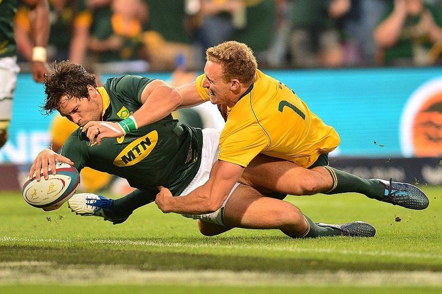 South Africa's Jan Serfontein muscling his way past Australia's Reece Hodge to score a try during the Rugby Championship match in Bloemfontein, South Africa last week. The Springboks were held to a 27-27 draw and will next face the All Blacks on Satu