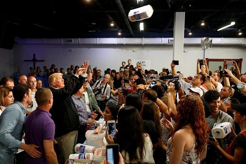 President Donald Trump tossing rolls of paper towels to people at a hurricane relief distribution centre at Calvary Chapel in San Juan, Puerto Rico, on Tuesday. Mr Trump and his wife Melania visited the middle-class suburb of Guaynabo, mingled with s