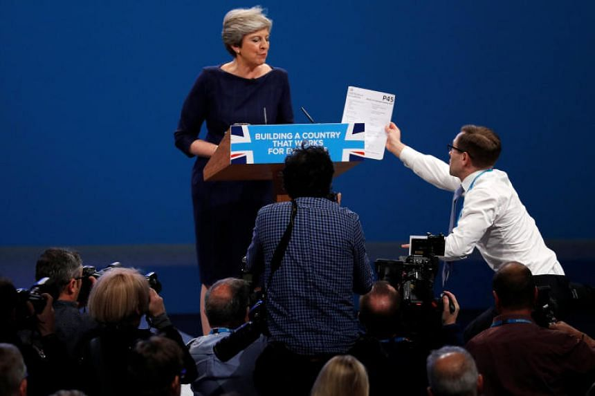 A member of the audience hands a P45 form (termination of employment tax form) to Britain's Prime Minister Theresa May as she addresses the Conservative Party conference in Manchester on Oct 4, 2017.