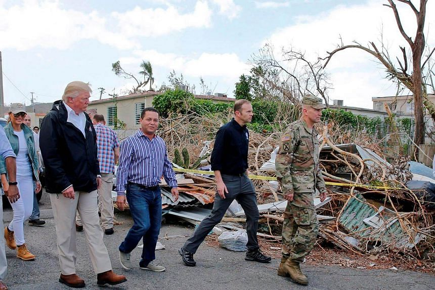 US President Donald Trump walks past hurricane wreckage as he participates in a walking tour in areas damaged by Hurricane Maria in Guaynabo, Puerto Rico.