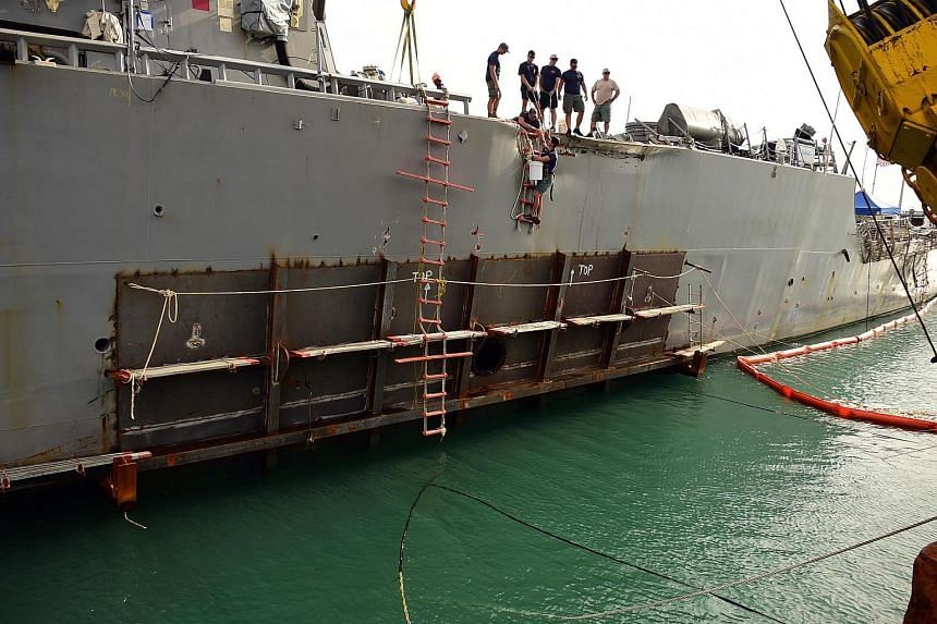 USS John S. McCain is pictured at Changi Naval Base in Singapore after a temporary patch was welded to the area damaged by the collision.