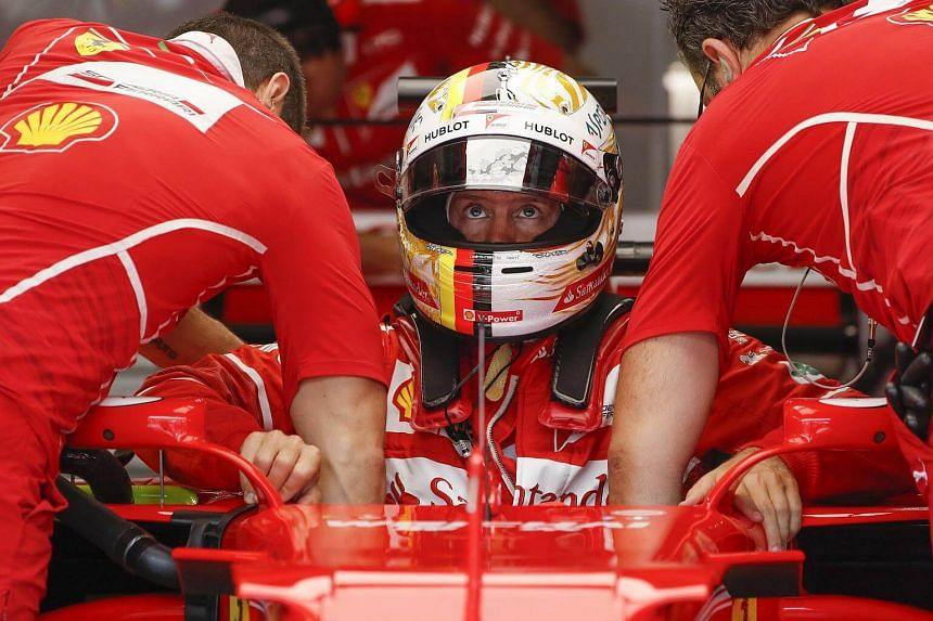 Sebastian Vettel of Scuderia Ferrari gets into his car during the third practise session for the Malaysian Formula One Grand Prix.