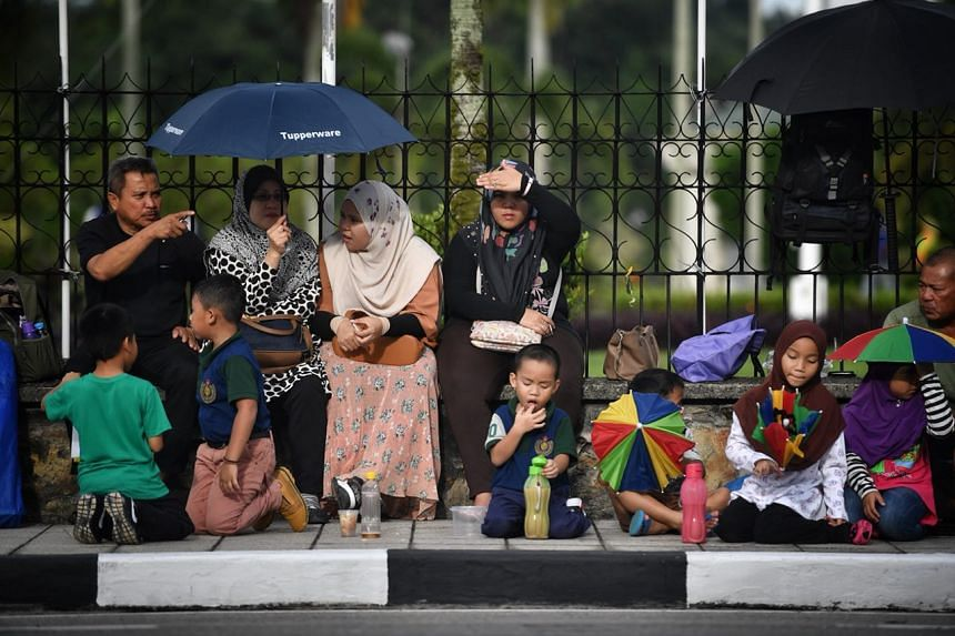 Crowds line the streets while waiting for the Golden Jubilee royal procession to start.