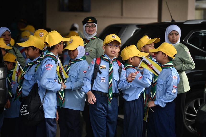Students hold up Brunei flags while waiting for the Golden Jubilee royal procession to start.