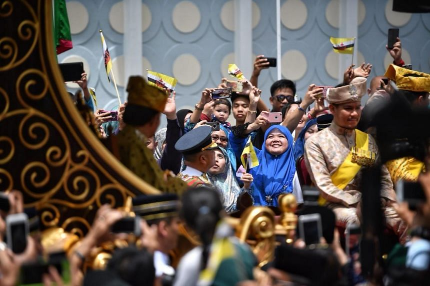 The crowd cheers as Sultan of Brunei Hassanal Bolkiah goes through the city during the Royal Procession.