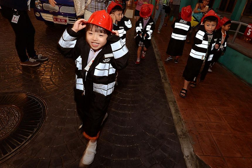 Children role-play as firemen at KidZania Singapore in April 2016.