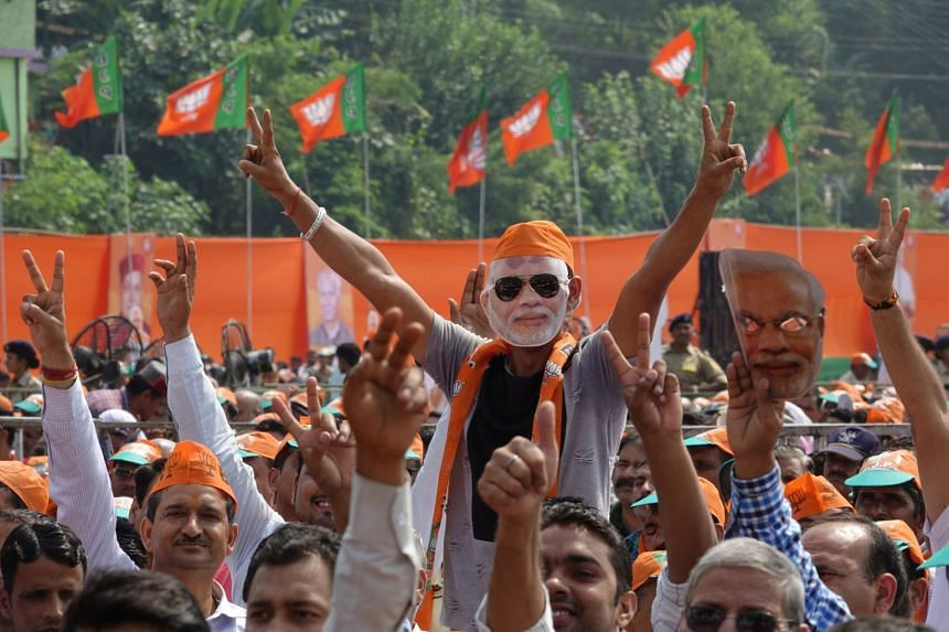 A supporter in a mask bearing Indian Prime Minister Narendra Modi's likeness attending a BJP rally in Bilaspur, Chhattisgarh, on Tuesday, ahead of state assembly elections. Mr Modi was also in the state to lay the foundation stone for All India Insti