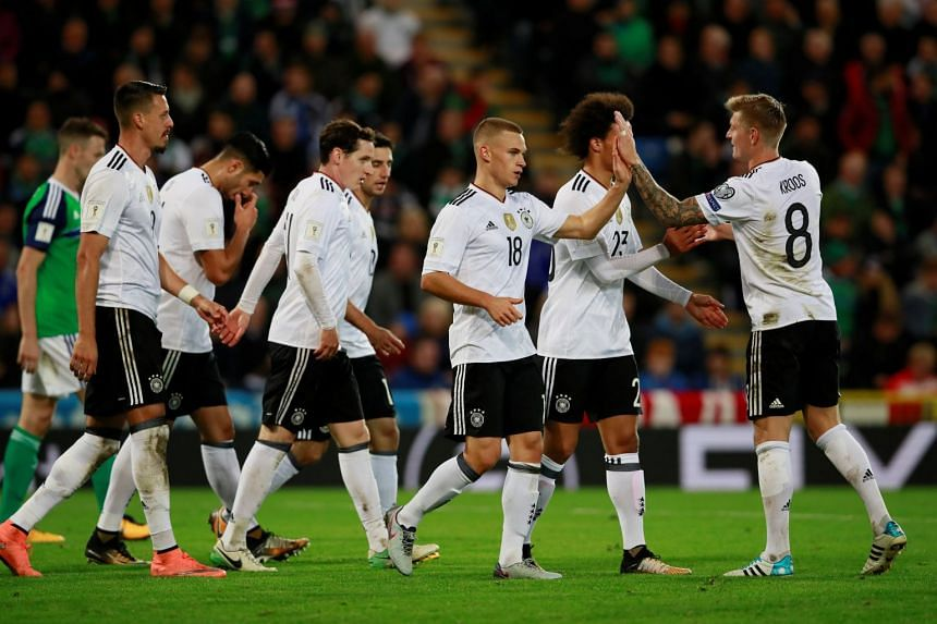 Germany's Joshua Kimmich celebrates with team mates after scoring their third goal.