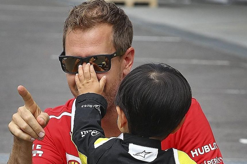 Clockwise from far left: This supporter of former F1 driver Robert Kubica, Ferrari's Kimi Raikkonen and McLaren's Fernando Alonso is clearly no fair-weather fan. Mercedes driver Lewis Hamilton does not sign out when a Sebastian Vettel fan asks for hi