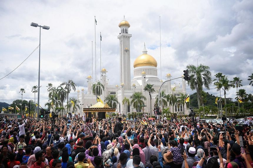 Above: Brunei Sultan Hassanal Bolkiah with his wife, Raja Isteri Pengiran Anak Hajah Saleha, at the throne hall of Istana Nurul Iman for the Golden Jubilee ceremony yesterday. Left: A huge crowd of people gathered in the streets of Bandar Seri Begawa