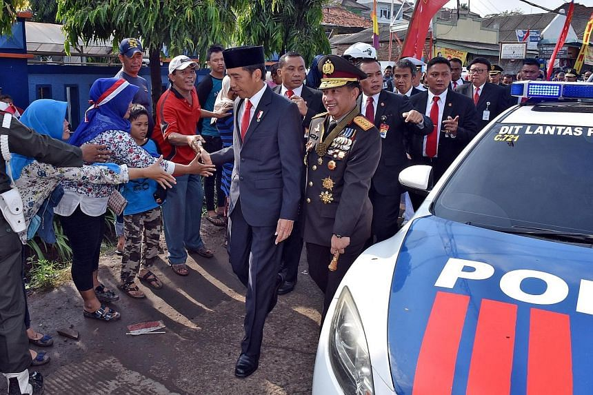 President Joko Widodo shaking hands with villagers as he walked the rest of the way - about 2km - to the venue for a military parade to mark the 72nd anniversary of Indonesia's national armed forces in Cilegon, Banten province, yesterday. He had got