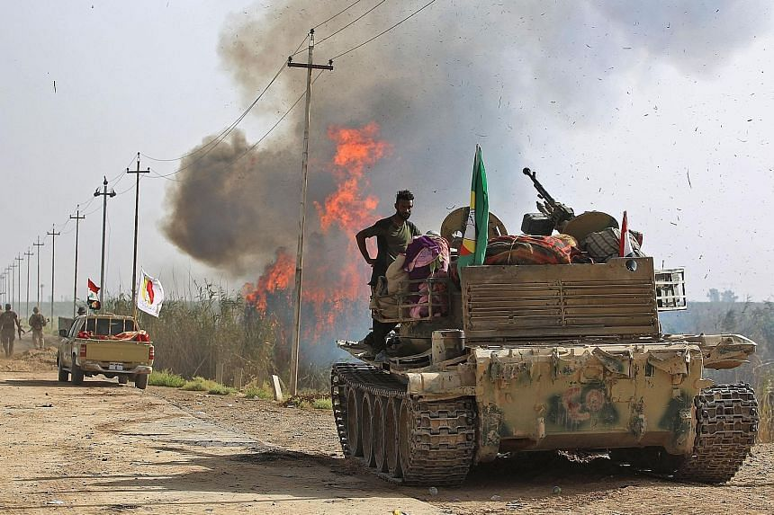 Fighters from the militia group Hashed al-Shaabi (Popular Mobilisation Units) and Iraqi forces advancing through Hawija yesterday after retaking the city from fighters of the terrorist group Islamic State in Iraq and Syria (ISIS). Iraqi forces overr