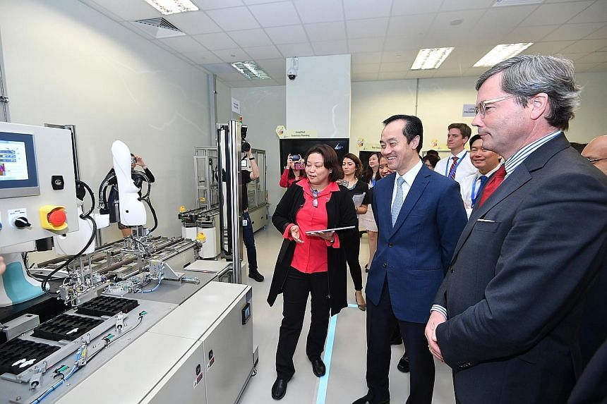 Senior Minister of State for Trade and Industry and National Development Koh Poh Koon (centre) with German Ambassador Ulrich Sante (right) at the A*Star model factory located in one-north. They are viewing some of the equipment which manufacturers ca